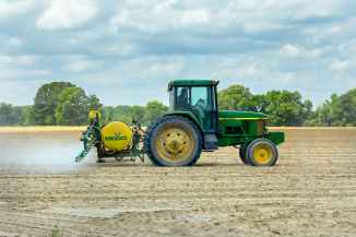 green and yellow tractor on dirt